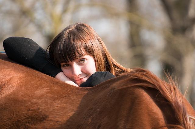 slečna opřená o hřbet koně