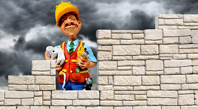 Figurka stavebníka držícího v ruce plány